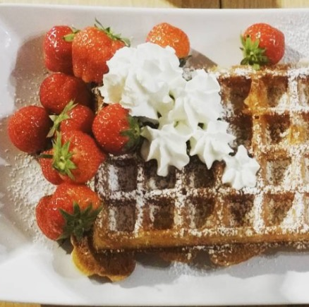some delicious waffle with strawberries and cream on top