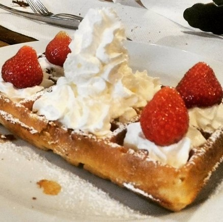 big pile of cream and strawberries on a waffle in Belgium